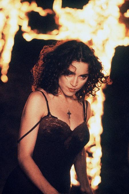 Cantora Madona usa crucifíxo com fogo de fundo