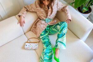 Mulher com calça psicodélica em tons de verde