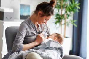 Mulher amamentando bebê.